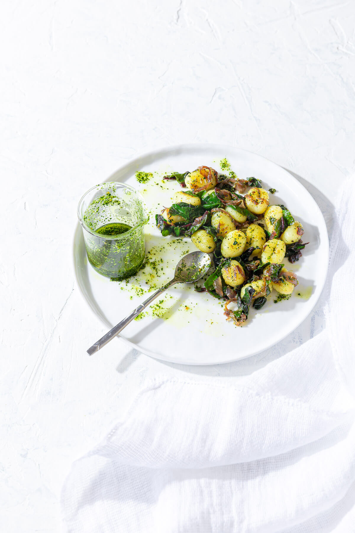 Plate of gnocchi with sautéed greens and kale pesto shown with a jar of extra pesto and a spoon.