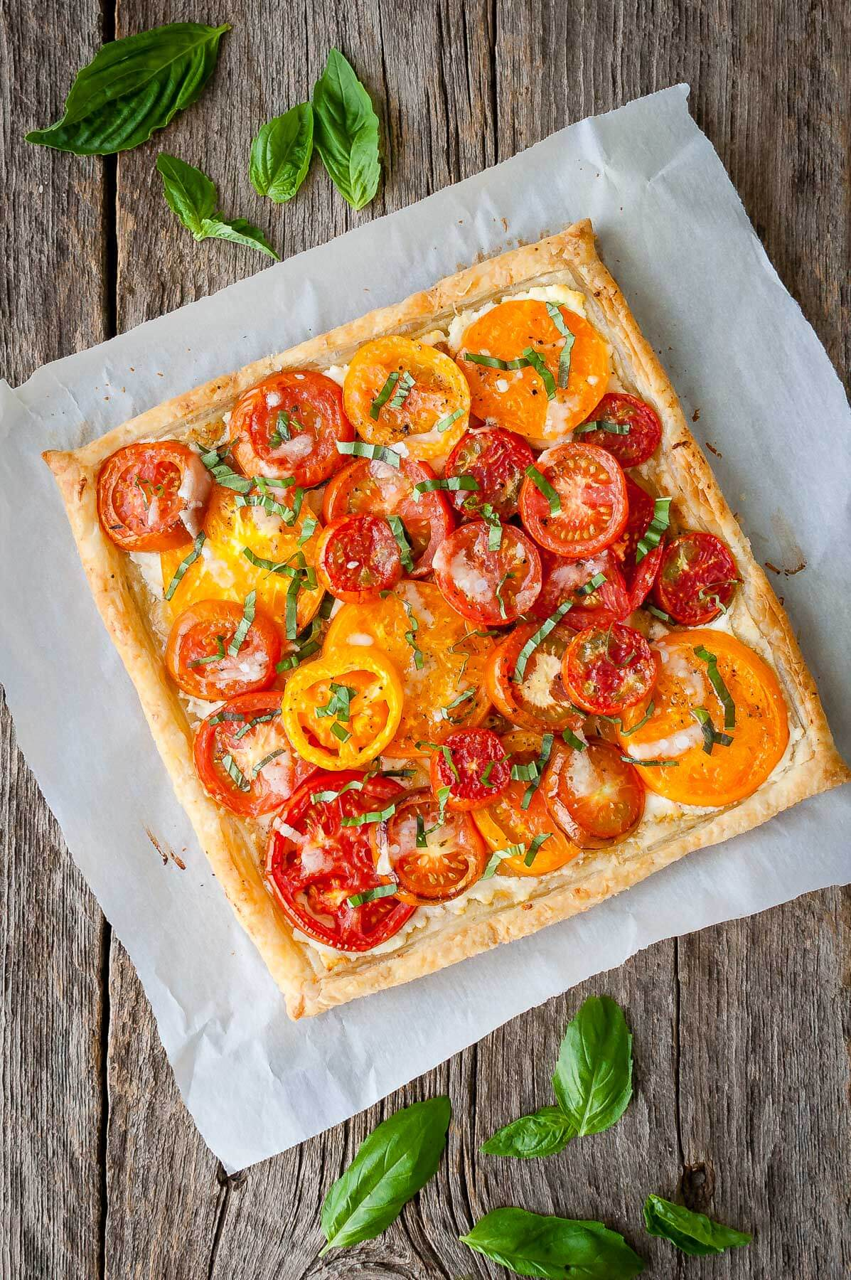 Tomato tart with goat cheese and caramelized onions on a piece of parchment paper with loose basil leaves.