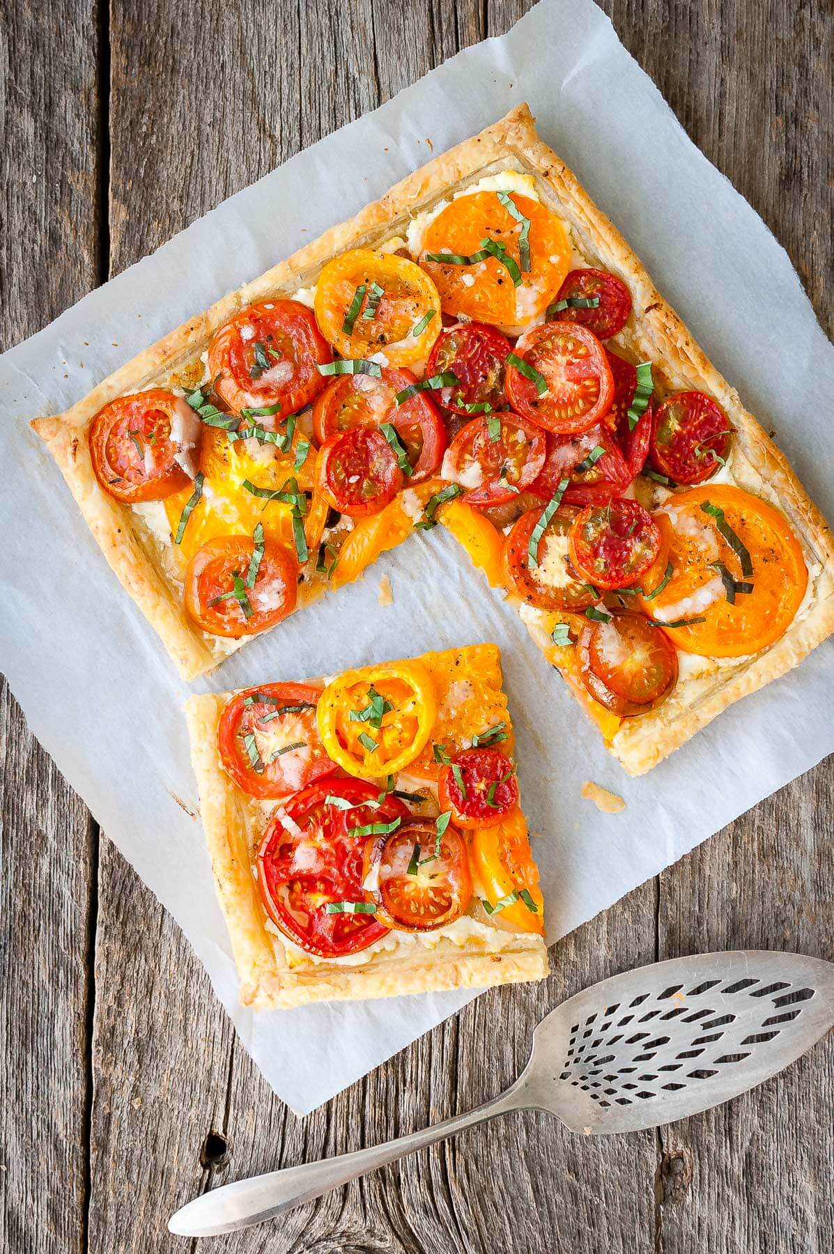 Tomato tart with goat cheese and caramelized onions on a piece of parchment paper.