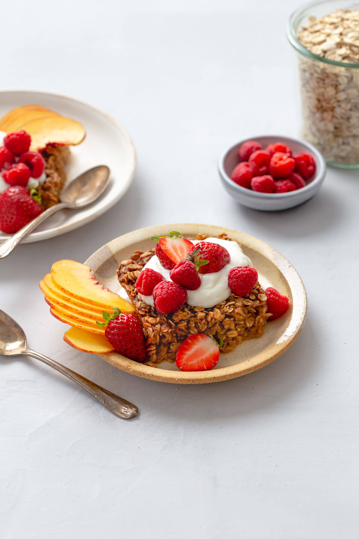 Plate of baked oatmeal topped with yogurt and fresh fruit.