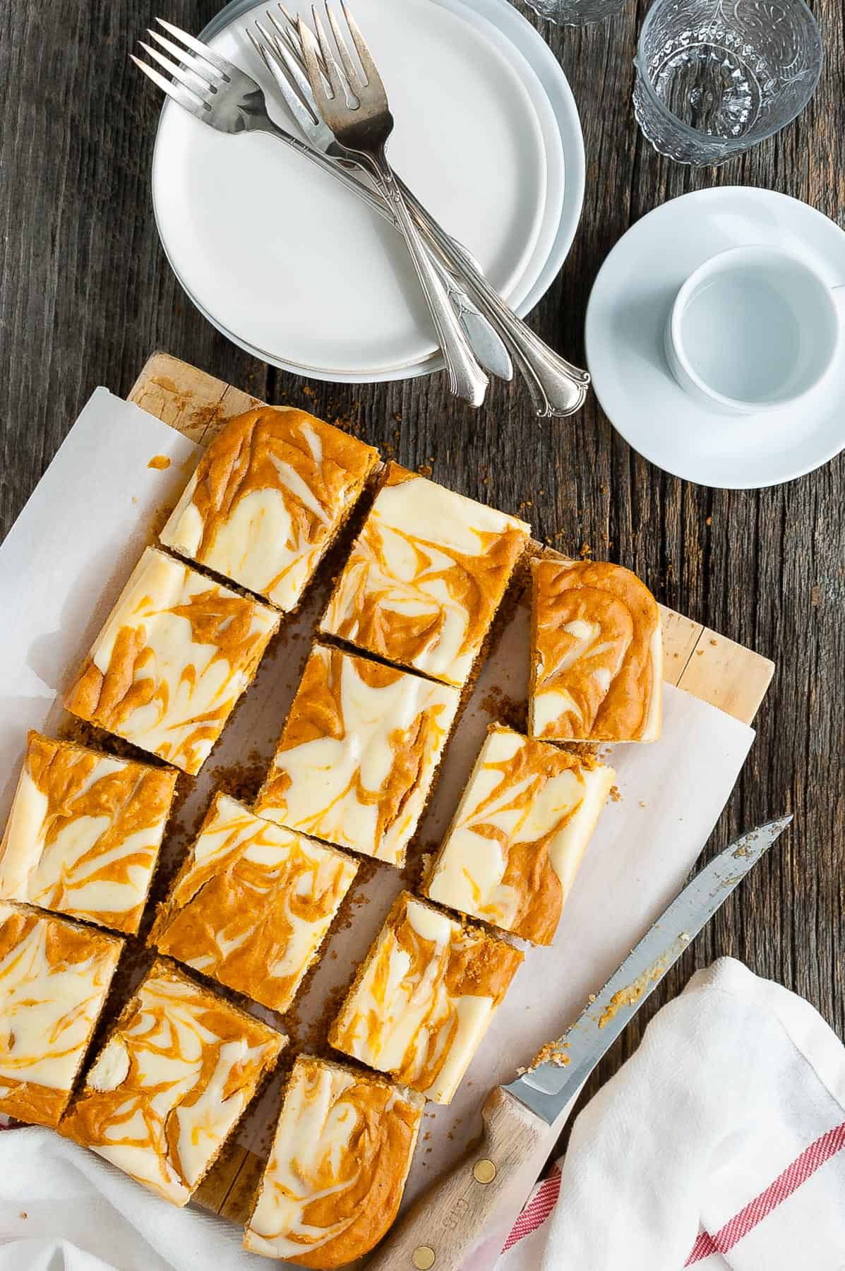 Several slices of marbled pumpkin cheesecake bars on a serving board.