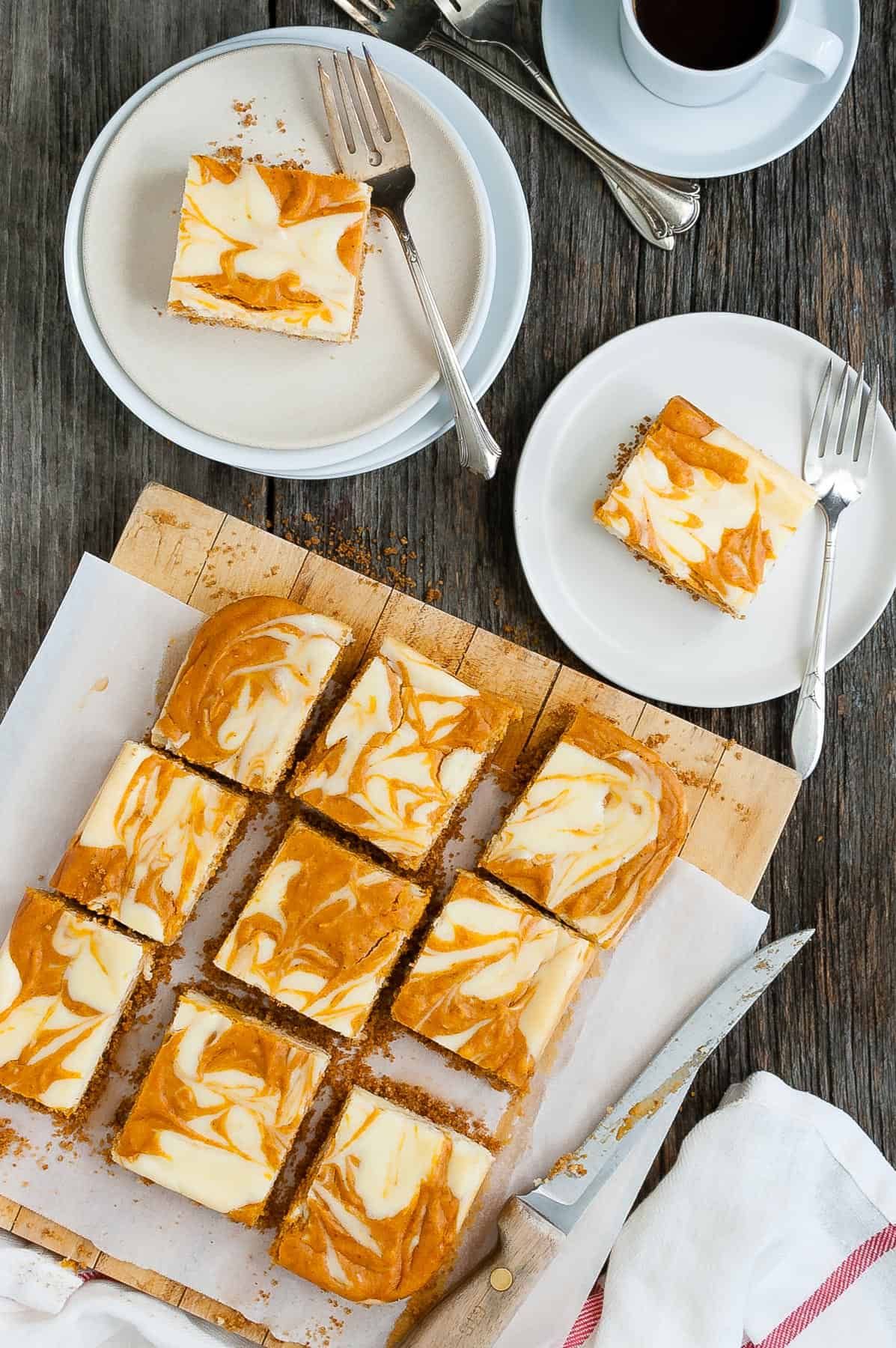 Several slices of marbled pumpkin cheesecake bars on a serving board plus two slices on plates.