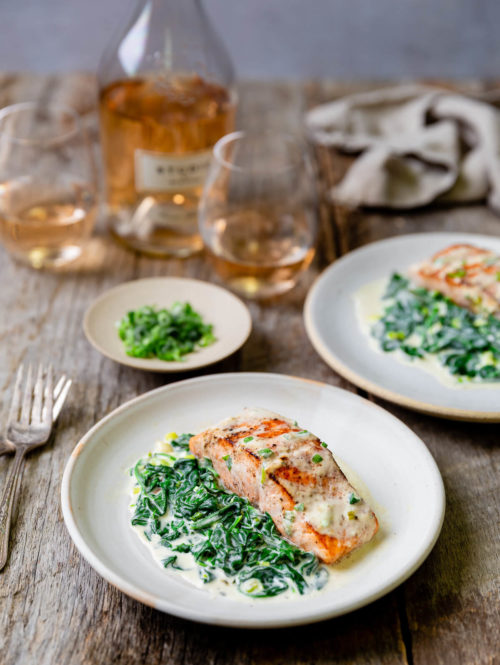 Two plates of pan seared salmon with creamed spinach on the side.
