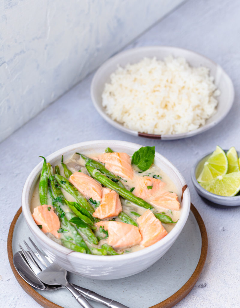 Bowl of salmon in coconut-miso broth with green beans served with a bowl of rice.