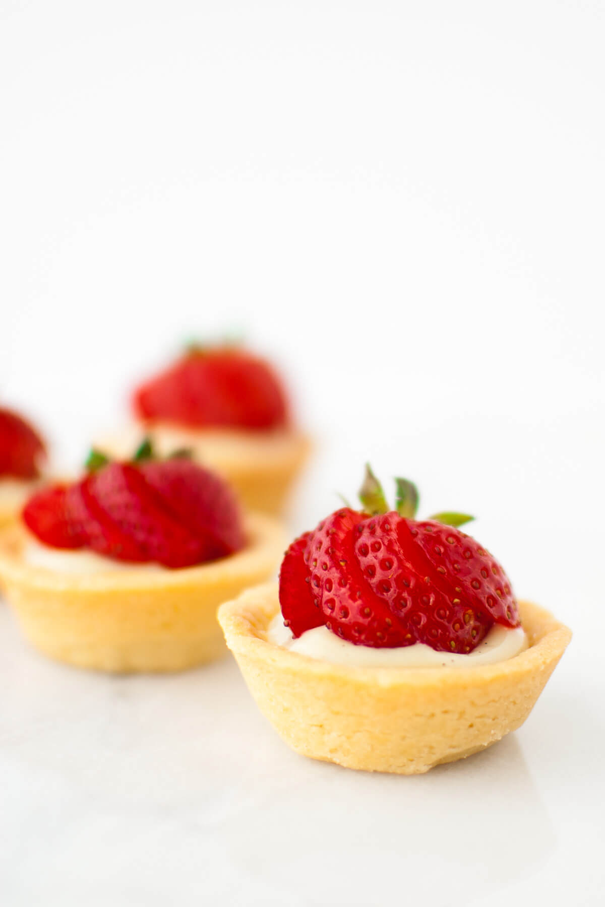 A close-up shot of mini fruit tartlets with vanilla pastry cream and strawberries.