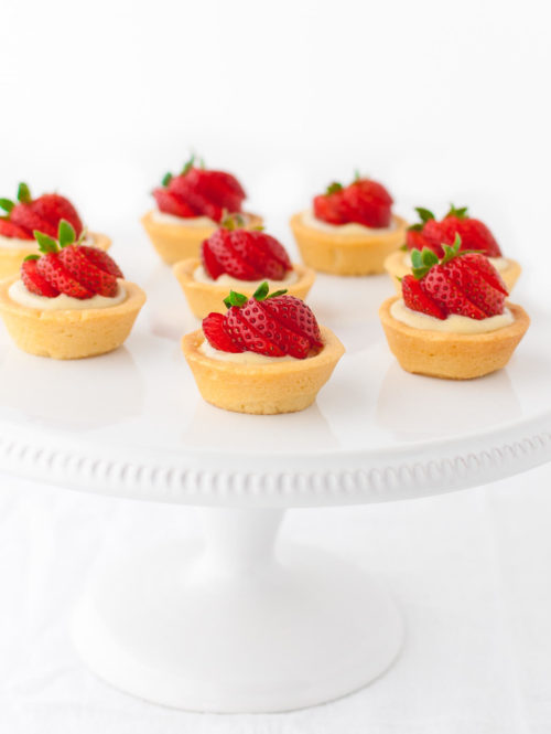 Several mini strawberry tartlets on a white cake stand.