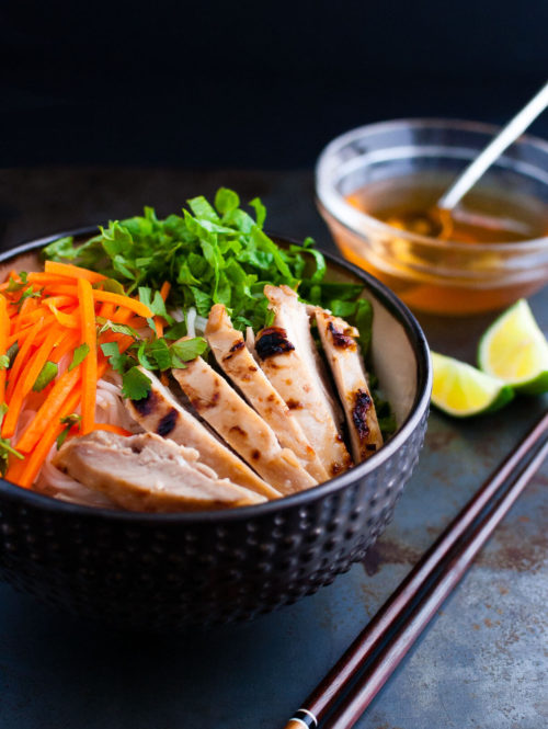 Vietnamese noodles with marinated grilled chicken in a bowl served with fresh lettuce, herbs, and fish sauce.