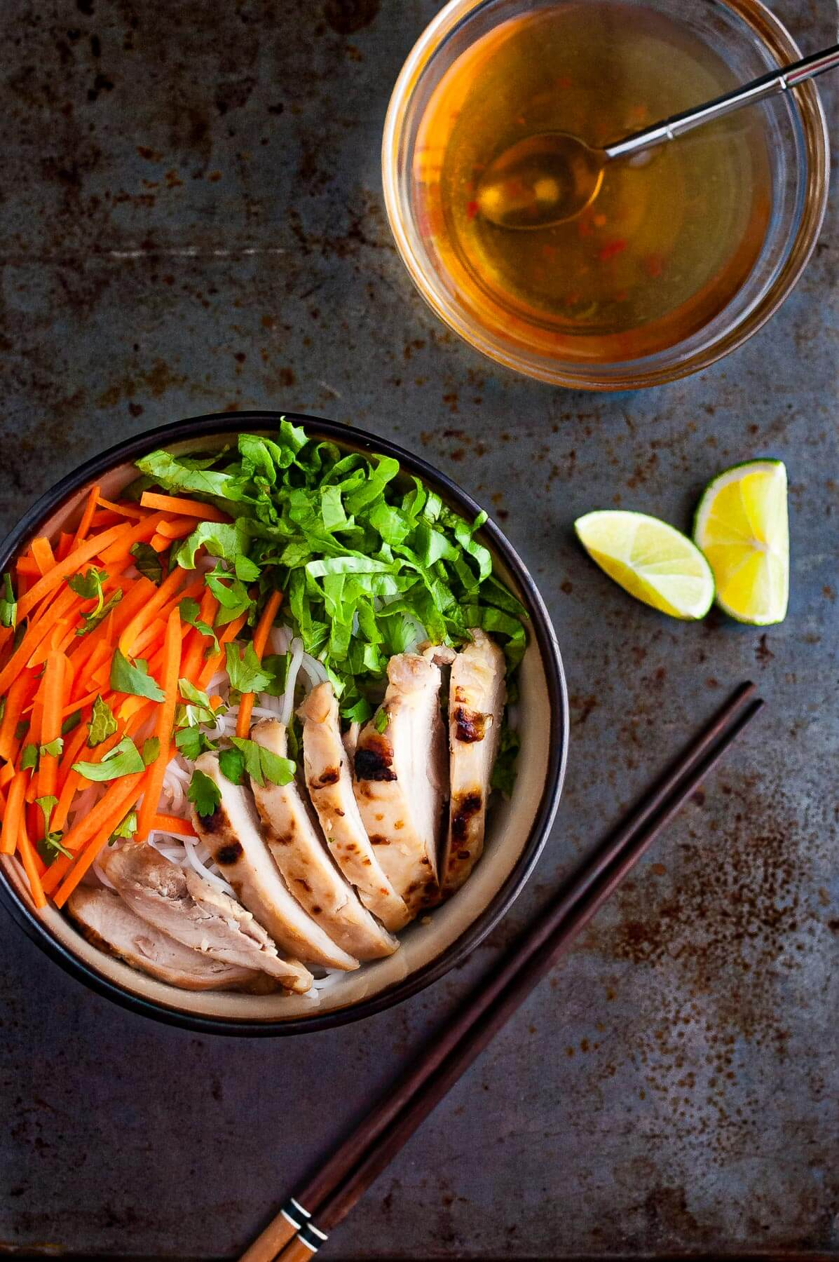 Overhead photo of Vietnamese noodles with grilled chicken in a bowl served with fresh lettuce, herbs, and fish sauce.