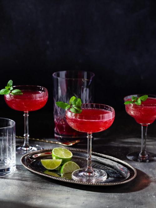 Several glasses of sparkling ginger pomegranate mocktail on a dark table.