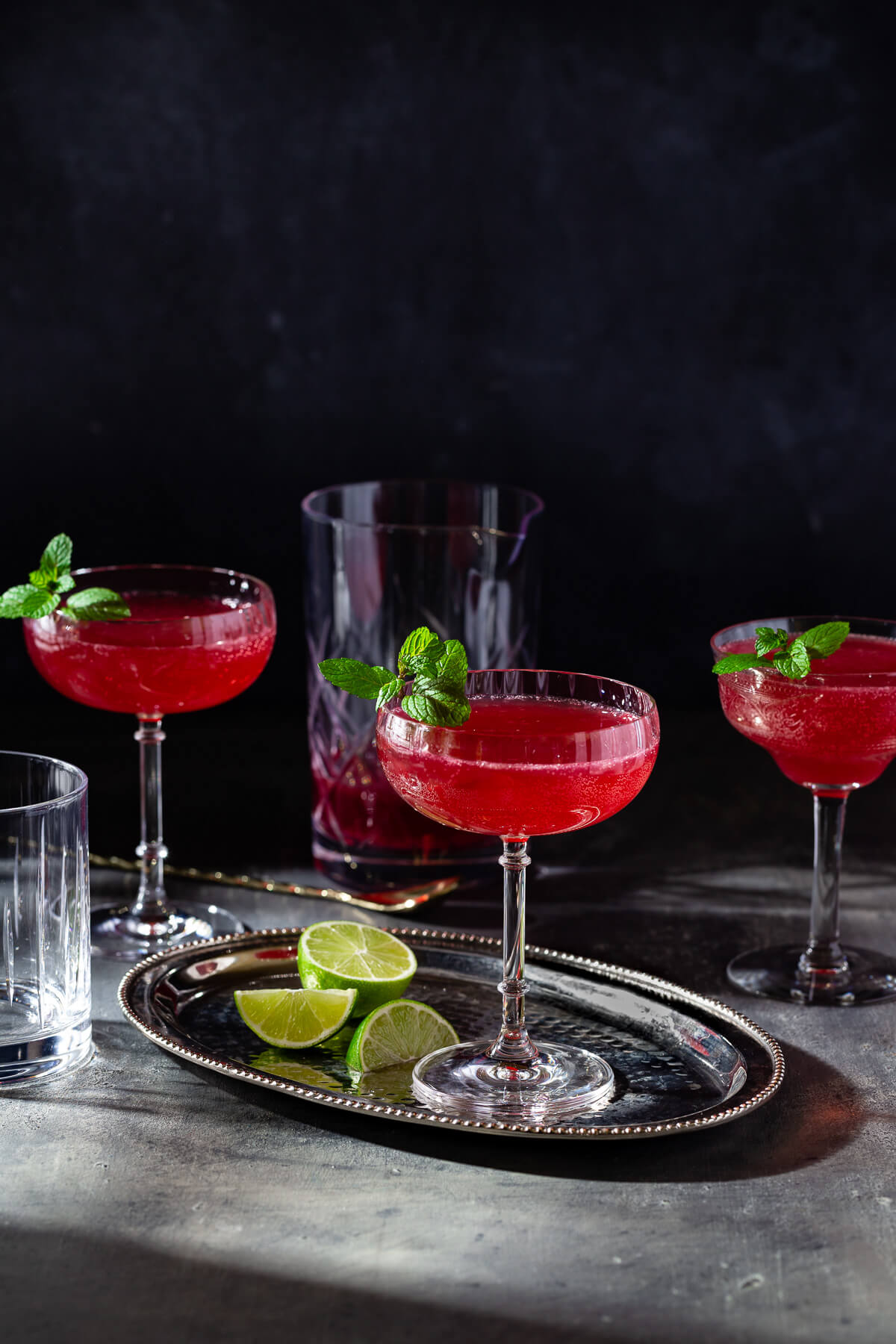 Several glasses of sparkling ginger pomegranate mocktail on a dark table.