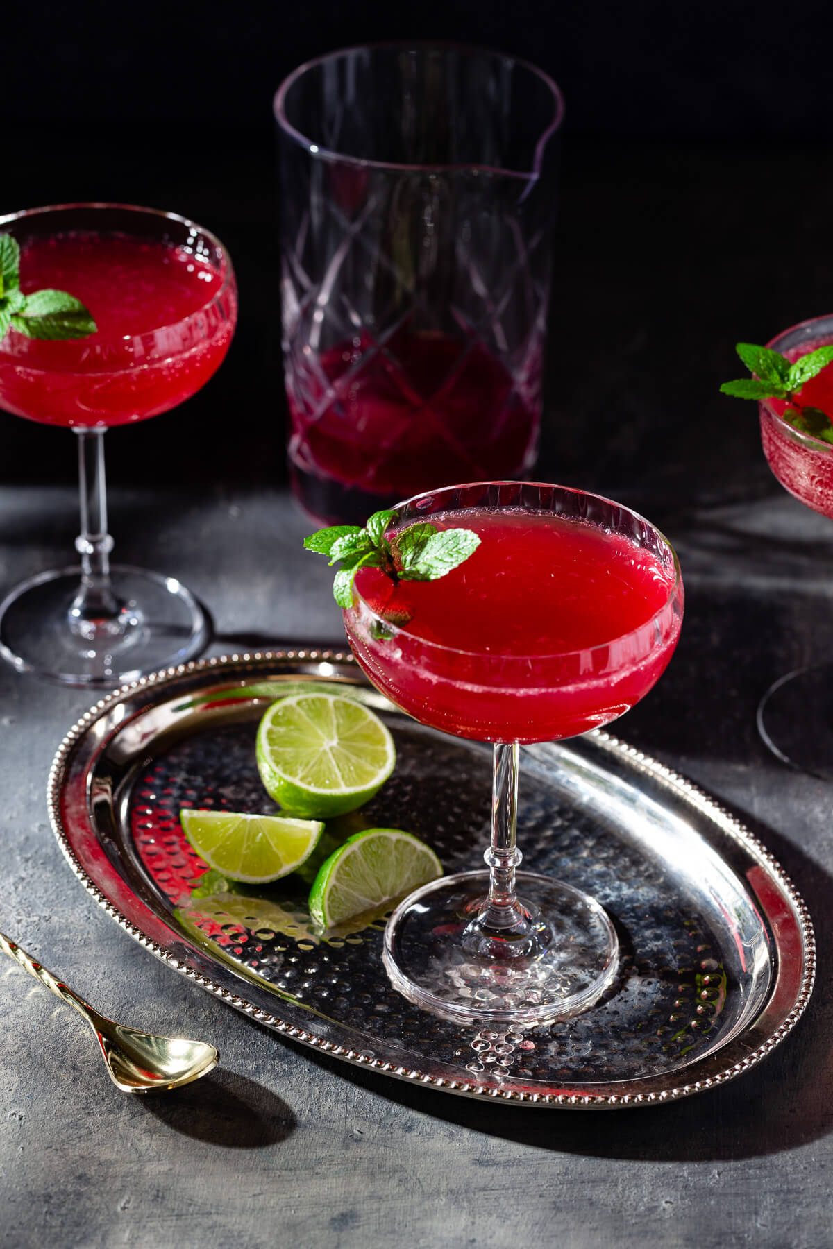 A glass of sparkling ginger pomegranate mocktail on a silver tray.