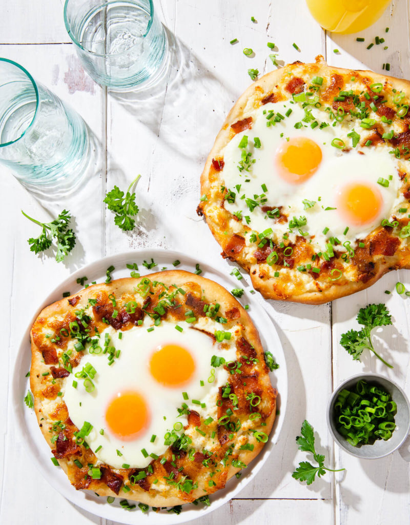 Overhead view of two breakfast pizzas on a white board.