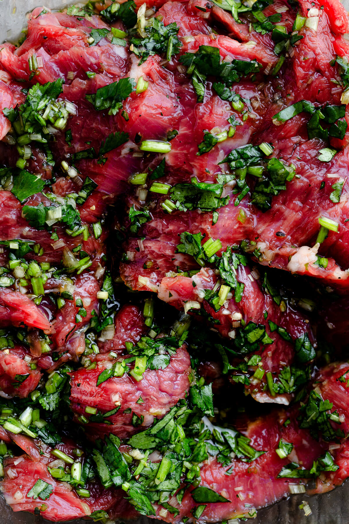 Slices of flank steak marinating in a marinade of lemongrass, cilantro, and fish sauce.