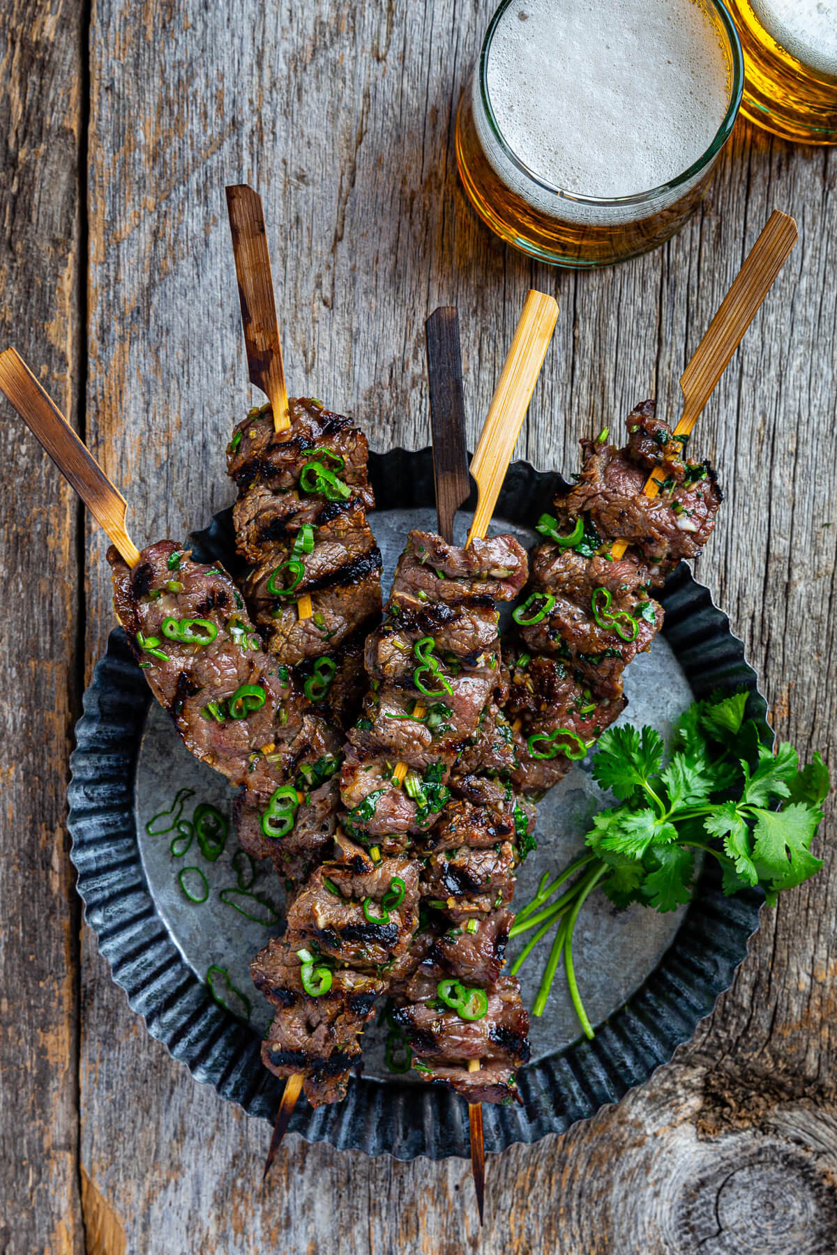 Overhead view of several grilled beef skewers on a metal serving dish.