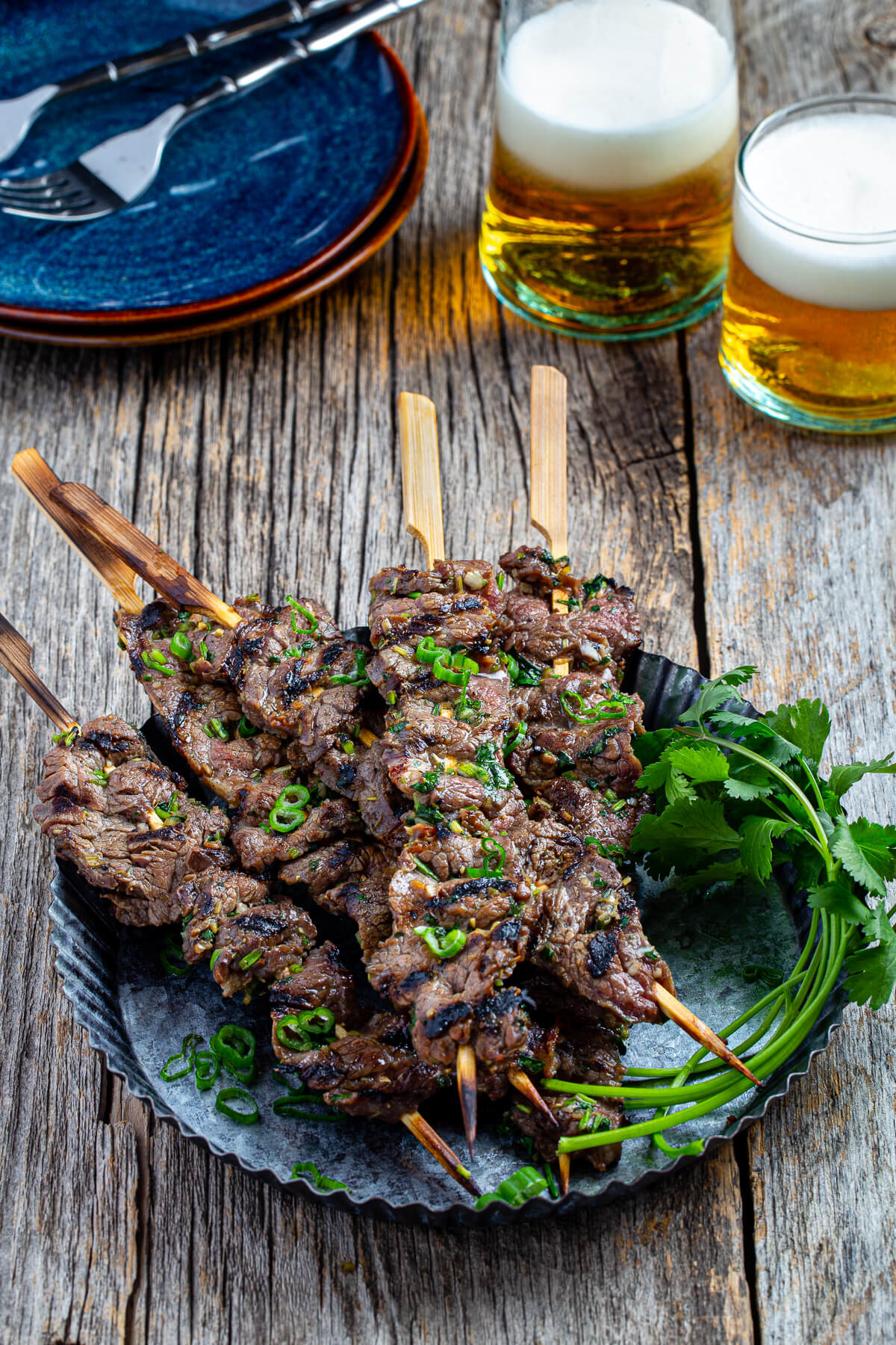Skewers of grilled beef on a metal serving dish served next to glasses of beer.