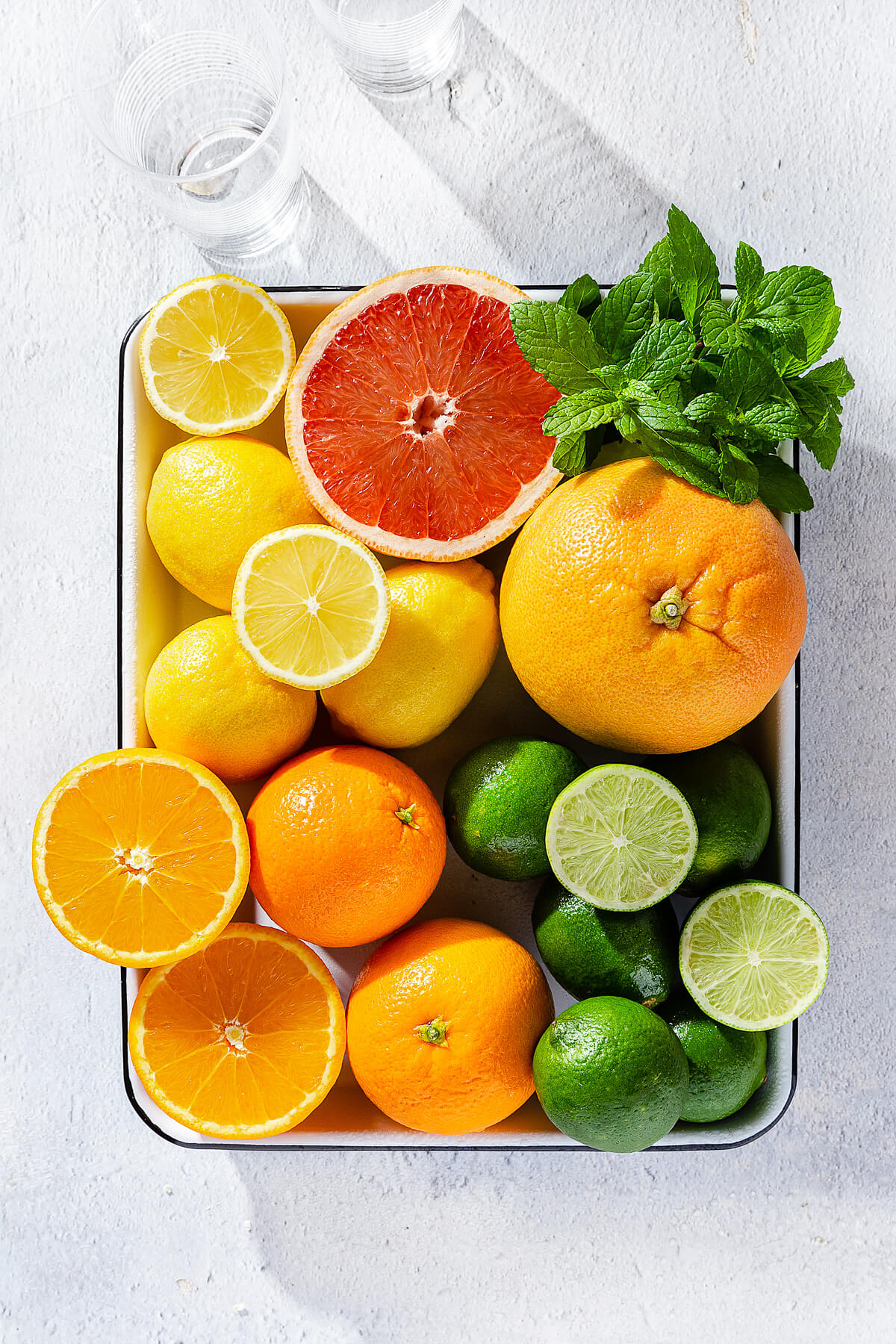 A tray of citrus fruits - oranges, grapefruit, lemon, and limes and some fresh mint.