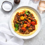 Overhead view of cherry tomato ragout and polenta in a serving dish next to some glasses of rosé.