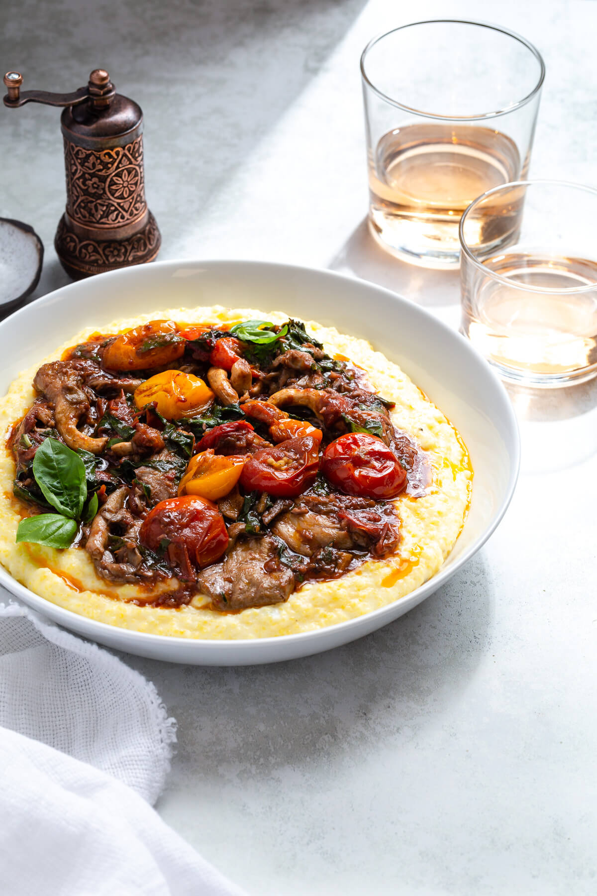 Some cherry tomato ragout and polenta in a serving dish next to some glasses of rosé.