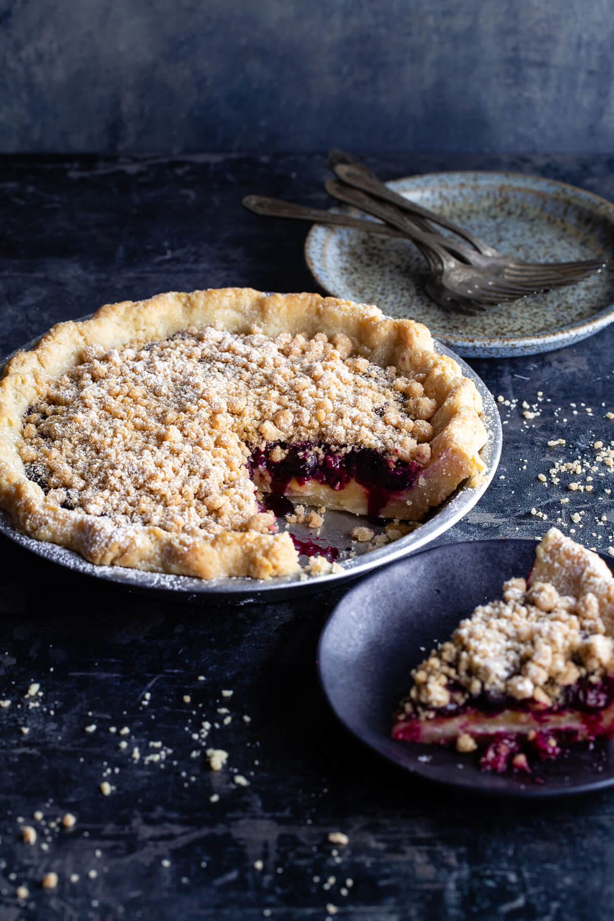 A lemon-blueberry streusel pie with a slice taken out next to a slice of pie on a plate.