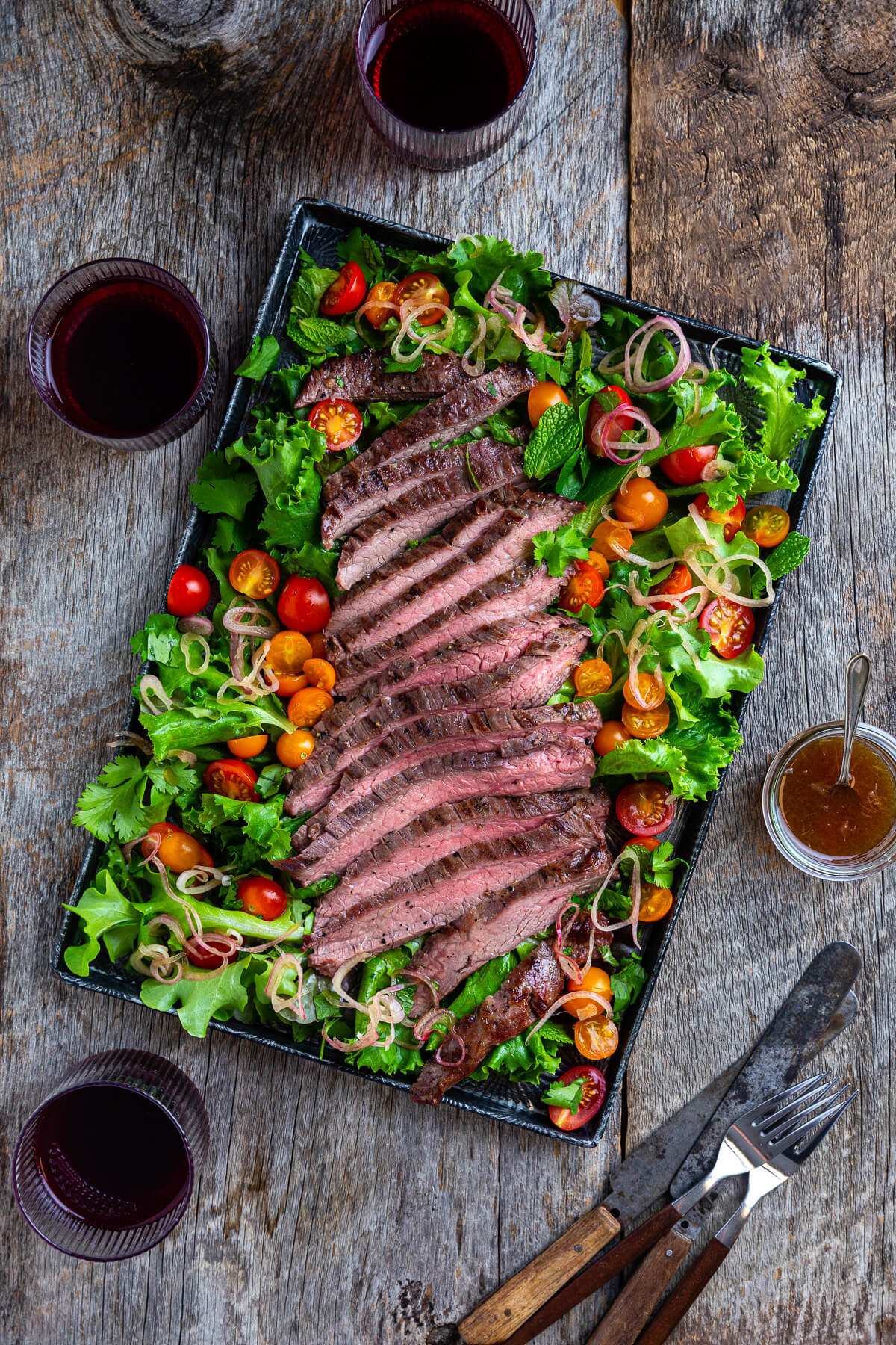 Overhead view of sliced Thai beef with salad greens, tomatoes, and, fresh herbs on a metal tray.