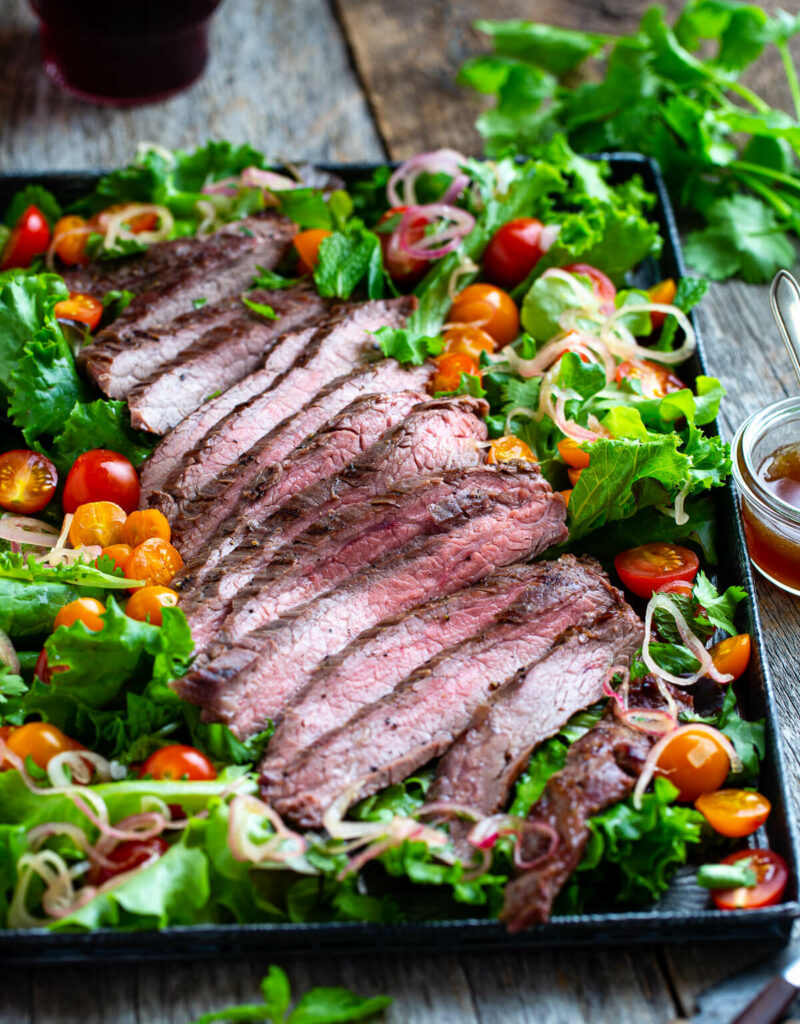Sliced Thai beef with salad greens, tomatoes, and, fresh herbs on a metal tray with extra dressing on the side..