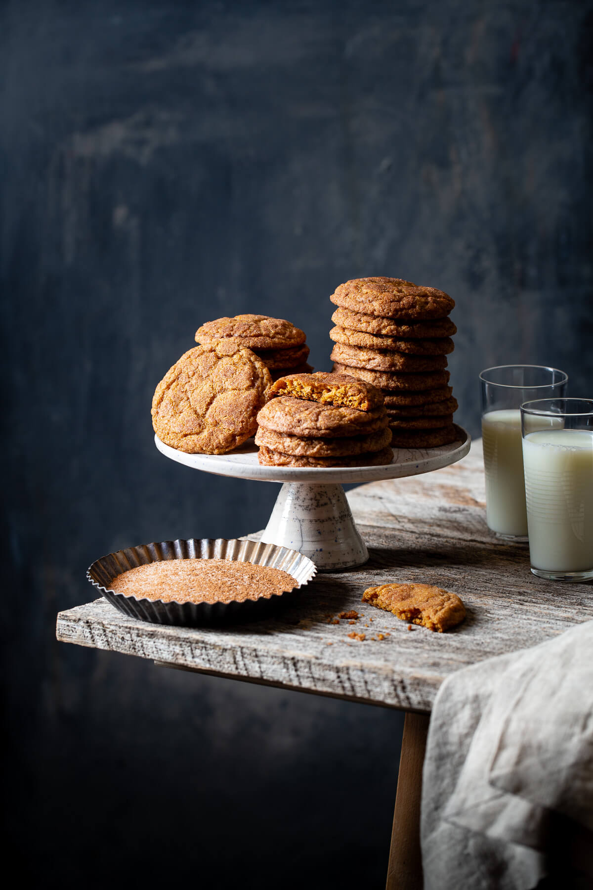 Stacks of pumpkin snickerdoodle cookies on a cake stand.